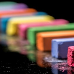 Close up row of colorful chalk isolated on black background. Macro photography. Cut out