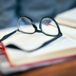 Closeup shot of reading glasses on an open book on a university desk indoors